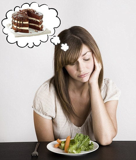 A woman thinking over a plate of healthy food and thinking about a cake, counting the calories in the cake